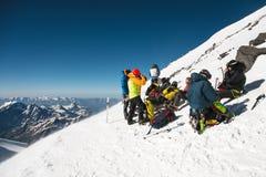 Les alpinistes professionnels entièrement équipés sur un arrêt s'asseyent sur une pente neigeuse par temps ensoleillé Image libre de droits