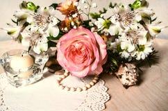 Les Alstroemerias avec jaune-rose ont monté, les perles, chandelier en cristal avec la serviette modelée Photo libre de droits