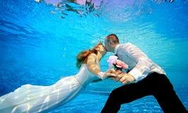 Les amants équipent et femme dans des robes de mariage embrassant l'eau du fond dans la piscine et tenant des fleurs dans sa main Photographie stock libre de droits