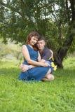 Les amants équipent et femme s'asseyant à la nuance d'un arbre feuillu Photos stock