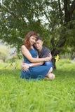 Les amants équipent et femme s'asseyant à la nuance d'un arbre feuillu Images libres de droits