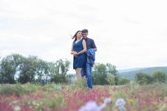Les amants équipent et la promenade de femme sur le champ avec les fleurs rouges Photos stock
