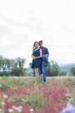 Les amants équipent et la promenade de femme sur le champ avec les fleurs rouges Photo libre de droits