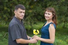 Les amants équipent et le support de femme à la nuance d'un arbre feuillu Photos libres de droits