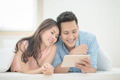 Les amants asiatiques de couples ont plaisir à observer le film en ligne sur le comprimé intelligent Photographie stock libre de droits