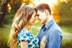 Les amants ayant touché leurs têtes sont dans les derniers rayons du soleil sur le champ Images libres de droits