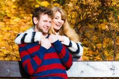 Les amants couplent en parc d'automne sur le banc photo stock