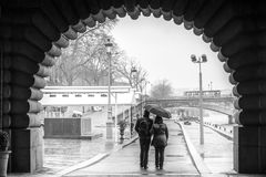 Les amants couplent la marche sur le quai de Sein à Paris pendant un jour pluvieux Photos stock