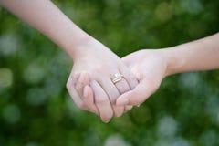 Les amants couplent tenir des mains avec le fond de bokeh pour l'amitié Images stock
