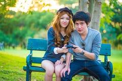 Les amants de jeu s'asseyent sur un banc entouré par nature Photo stock