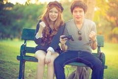 Les amants de jeu s'asseyent sur un banc entouré par nature Photographie stock libre de droits