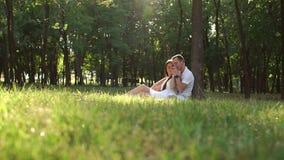 Les amants de jeune adolescent s'asseyent sur l'herbe se penchant contre un arbre en parc clips vidéos