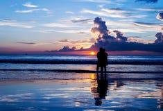 Les amants de silhouette détendent sur la plage Photo libre de droits