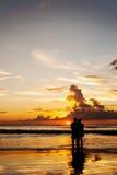Les amants de silhouette détendent sur la plage en couleurs de coucher du soleil Image stock