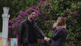 Les amants marchent admirablement en parc tenant des mains banque de vidéos
