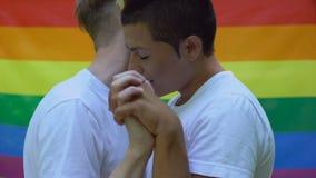 Les amants masculins appréciant la proximité, se tenant remet le fond de drapeau de lgbt, acceptation banque de vidéos