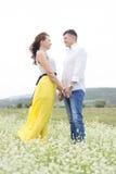 Les amants équipent et la promenade de femme sur le gisement de fleur Photo libre de droits