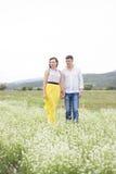 Les amants équipent et la promenade de femme sur le gisement de fleur Image libre de droits