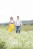 Les amants équipent et la promenade de femme sur le gisement de fleur Image stock