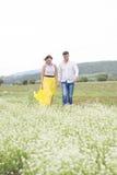 Les amants équipent et la promenade de femme sur le gisement de fleur Photos stock