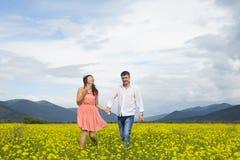 Les amants équipent et la promenade de femme sur le gisement de fleur Photo stock