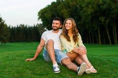 Les amants s'asseyent sur l'herbe et étreindre Photos libres de droits