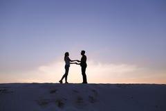 Les amants se tiennent des bras et remous sur la colline arénacée dans le désert dessus Image stock