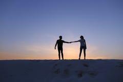 Les amants se tiennent des bras et remous sur la colline arénacée dans le désert dessus Photos libres de droits