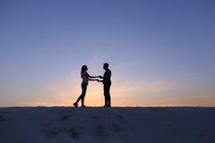 Les amants se tiennent des bras et remous sur la colline arénacée dans le désert dessus Photos stock