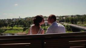 Les amants type et fille embrassent doucement sur les lèvres se reposant sur un banc sur la haute banque de la rivière Cadre très banque de vidéos