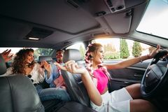 Les amies à la mode, élégantes, à la mode entrent dans la voiture écoutant la musique et ayant l'amusement ensemble Ils vont fair Photo libre de droits