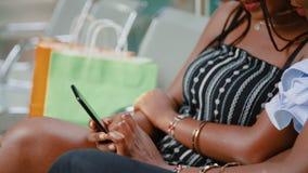 Les amies africaines s'asseyant sur le banc dans le mail clips vidéos