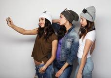 Les amies d'adolescentes dans l'équipement de hippie font le selfie à un téléphone Photos stock