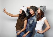 Les amies d'adolescentes dans l'équipement de hippie font le selfie à un téléphone Images stock