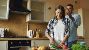 Les amies de bâche de jeune homme observe avec des mains et étonnant elle dans la cuisine à la maison Photographie stock