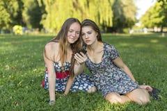 Les amies de jeunes filles utilisent le smartphone tout en se reposant dans le parc Image stock