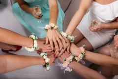 Les amies de la jeune mariée et de la jeune mariée s'asseyent en cercle et tiennent des mains Des mains sont décorées de la fleur Photo libre de droits
