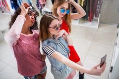 Les amies de sourire utilisant les lunettes de soleil élégantes ayant l'amusement chronomètrent prendre le selfie avec le télépho Images libres de droits