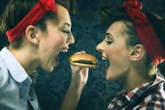 Les amies de vintage dans la robe de style ancien mangent des hamburgers Photographie stock