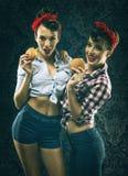 Les amies de vintage dans la robe de style ancien mangent des hamburgers Photos libres de droits