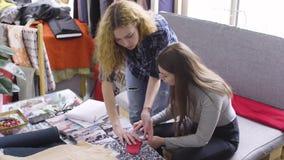 Les amies discutent de nouvelles conceptions des vêtements dans l'atelier clips vidéos