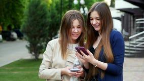 Les amies franches utilisent des smartphones regardant une photo, jeu, application, achats en ligne banque de vidéos