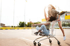 Les amies heureuses de femmes ont l'amusement avec des chariots à achats Photographie stock libre de droits