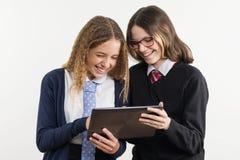 Les amies heureuses de lycée sont des adolescentes, regardent le comprimé Photos libres de droits