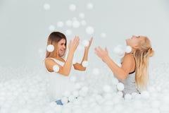Les amies heureuses de portrait se tiennent entourées par les boules en plastique blanches dans la piscine sèche Images stock