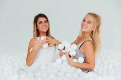Les amies heureuses de portrait se tiennent entourées par les boules en plastique blanches dans la piscine sèche Photos libres de droits