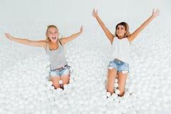 Les amies heureuses de portrait se tiennent entourées par les boules en plastique blanches dans la piscine sèche Image libre de droits