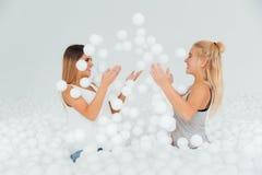 Les amies heureuses de portrait se tiennent entourées par les boules en plastique blanches dans la piscine sèche Photographie stock