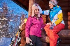 Les amies heureuses passent des vacances d'hiver au cottage de montagne Photos libres de droits