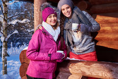 Les amies heureuses passent des vacances d'hiver au cottage de montagne Image libre de droits